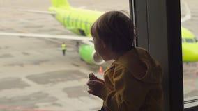 Slowmotion strzał młoda chłopiec je ciastko sittting przed dużym okno przy lotniskiem w żółtej kurtce zbiory
