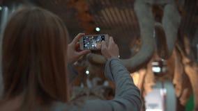 Slowmotion strzał młoda kobieta bierze obrazek mamutowy kościec na telefonie komórkowym zdjęcie wideo