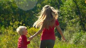 Slowmotion strzał młoda kobieta i jej mały syna bieg od gazonu mienia dalej wręcza wpólnie zbiory