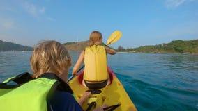 Slowmotion strzał młoda rodzina kayaking w tropikalnym morzu i ma zabawę patrzeje rafę koralową i tropikalne ryby zbiory
