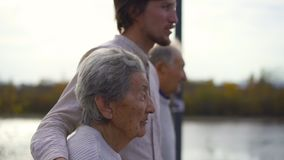 Slowmotion strzał młodego człowieka odprowadzenie z jego dziadkami na przejściu wzdłuż brzeg rzekiego zdjęcie wideo