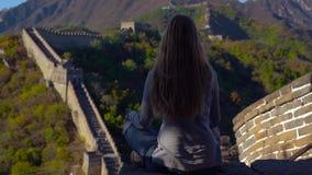 Slowmotion strzał młodej kobiety obsiadanie i medytować na górze Porcelanowego wielkiego muru Taravell Porcelanowy pojęcie zbiory