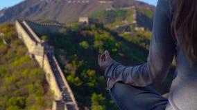 Slowmotion strzał młodej kobiety obsiadanie i medytować na górze Porcelanowego wielkiego muru Taravell Porcelanowy pojęcie zbiory wideo