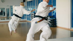 Slowmotion trick för karate för kvinna` s nära spegeln i idrottshallen lager videofilmer