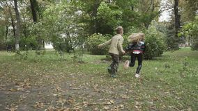 Cute children run in the park in slowmotion stock footage