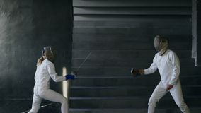 Slowmotion of Two fencers man and woman have fencing match indoors. Slowmotion of Two fencers man and woman have fencing competition indoors stock video footage