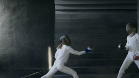Slowmotion of Two fencers man and woman have fencing training indoors. Slowmotion of Two fencers man and woman have fencing training before final competition stock video footage
