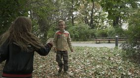 Children throws autumn leaves in the park. Slowmotion. Two pretty children are in the park. Curious boy and pretty girl throws the autumn leaves. Happy children stock video