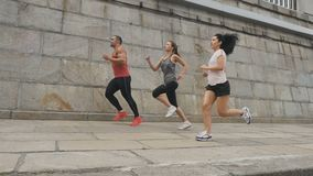 People have running at the embankment. Slowmotion. Two young women and handsome man stands at the embankment. Three people wearing sporty outfit start to run stock video footage