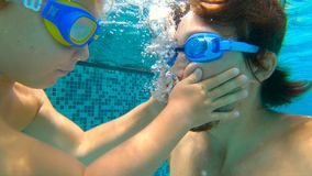 Slowmotion underwater shot of father and his toddler son swining diving and having fun in a pool. Slowmotion underwater shot of father and his toddler son stock video footage
