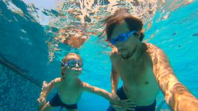 Slowmotion underwater shot of father and his toddler son swining diving and having fun in a pool. Slowmotion underwater shot of father and his toddler son stock footage