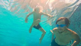 Slowmotion underwater shot of father and his toddler son swining diving and having fun in a pool.  stock footage