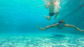 Slowmotion underwater shot of father and his toddler son swining diving and having fun in a pool.  stock video