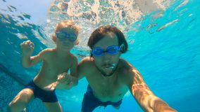 Slowmotion underwater shot of father and his toddler son swining diving and having fun in a pool.  stock video footage