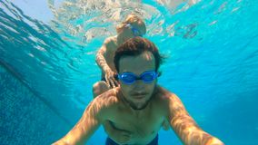 Slowmotion underwater shot of father and his toddler son swining diving and having fun in a pool. Slowmotion underwater shot of father and his toddler son stock video