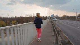 SlowMotion van de Jonge Vrouw van Nice in Sportkleding die op een Brug in de Stad lopen stock footage