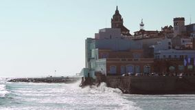 Slowmotion waves crashing in Sitges, Barcelona province, Spain. Slowmotion waves crashing in mediterranean town of Sitges, with the iconic Church of Santa Tecla stock video footage