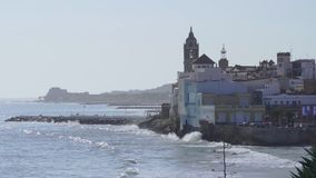 Slowmotion waves crashing in Sitges, Barcelona province, Spain. Slowmotion waves crashing in mediterranean town of Sitges, with the iconic Church of Santa Tecla stock footage