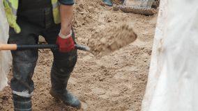 Slowmotion worker in rubber boots with shovel smoothing sand in trench stock video