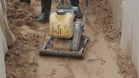 Slowmotion worker use gasoline plate compactor on sand in ditch at building site stock video