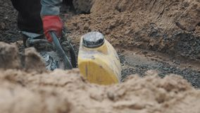 Slowmotion worker using plate compactor on macadam in ditch at building site stock footage