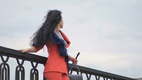 Pretty lady at the bridge. Slowmotion. Young brunette curly woman walks at the bridge. Attractive lady holds her wallet in the hands. Beautiful woman straightens stock video