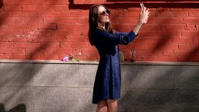 Slowmotion. A young woman in a blue dress at the red wall makes a selfie photo. Fashion smiling female in sunglasses taking self-portrait picture on smartphone stock video