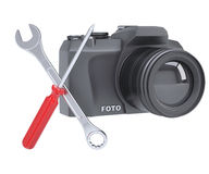 SLR camera, a screwdriver and a wrench Royalty Free Stock Photos