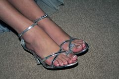 Woman`s feet in silver shoes stock image