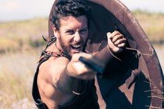 Slåss den forntida krigaren i harnesk med svärdet och skölden Royaltyfri Foto