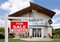 Sålt hem- till salu tecken framme av huset Fotografering för Bildbyråer