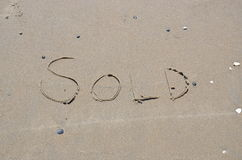 Sålt skriftligt i sanden på stranden Arkivbild