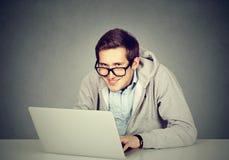 Slug oärlig man som använder en bärbar dator som konspirerar serversabotage royaltyfri foto