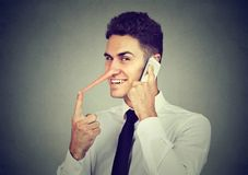 Slug ung man med den långa näsan som talar på mobiltelefonen på grå väggbakgrund Lögnarebegrepp royaltyfri fotografi