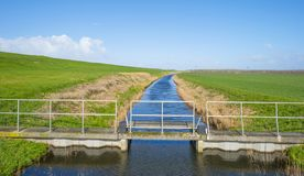 Sluice in a canal along a green dike below a blue sk. Y in winter royalty free stock photography