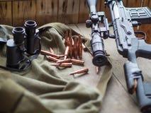 Sluipschuttergeweer, bunoculars en munitie die op houten vloer leggen royalty-vrije stock afbeeldingen