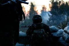 Sluipschutterteam met groot kaliber, sluipschuttergeweer wordt bewapend, die vijandelijke doelstellingen op waaier van schuilplaa royalty-vrije stock afbeeldingen