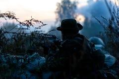 Sluipschutterteam met groot kaliber, sluipschuttergeweer wordt bewapend, die vijandelijke doelstellingen op waaier van schuilplaa stock afbeelding