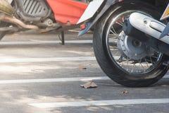 Sluit band van motorfiets op concrete vloer bij autoparkeerterrein dat bij openlucht omhoog wordt geparkeerd royalty-vrije stock afbeelding