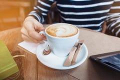 Sluit beeld van de handen van de vrouw tegenhoudt kop coffe en draagbaar aanrakingsstootkussen Het wijfje leest tekstbericht in s Stock Foto's