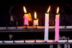 sluit brandwond omhoog roze en witte kaars aan het aanbieden/offer/ stock afbeeldingen