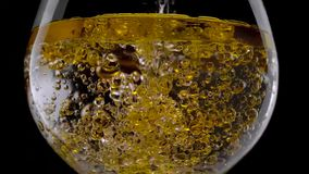 Sluit Champagne-omhoog bel in glas op zwarte achtergrond stock foto's