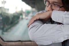 Sluit de eenzame gedeprimeerde Aziatische mens zitten en koesteren omhoog zijn knie op de vloer royalty-vrije stock foto