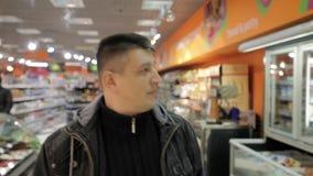 Sluit de gezichts omhoog jonge mens die in supermarkt lopen stock video