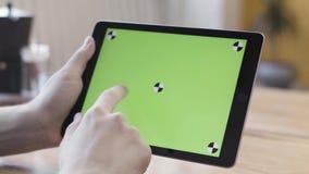 Sluit de handen van de mens die de digitale tabletcomputer vasthoudt met groen scherm, scrollen, glijden en tappen zijn apparaat stock videobeelden