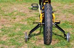 Sluit de jonge geitjes gele fiets in park, omhoog delen, achterband met remmen en extra wielen royalty-vrije stock afbeelding