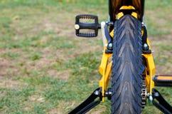 Sluit de jonge geitjes gele fiets in park, omhoog delen, achterband met remmen en extra wielen stock afbeelding