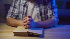 Sluit de mens zit bij een lijst en bestudeert een gebed stock footage
