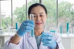 Sluit de omhoog geschotene, Aziatische wetenschappers van de midden-leeftijdsvrouw deskundige reageerbuis die onderzoek maken royalty-vrije stock afbeeldingen