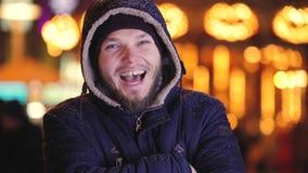 Sluit de omhoog glimlachende mens in nachtstad die zijn neus krast stock videobeelden